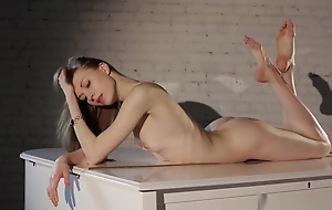 Melody. An nice-looking alterable ballerina widely spreads posing on the piano