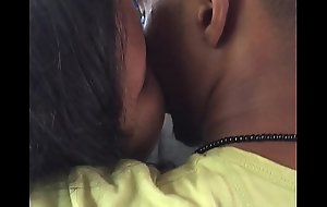 Legal age teenager couple giving a kiss back bus
